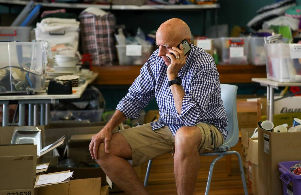 Former ESA boss Peter Dunn works the phones at the bushfire relief centre in Lake Conjola, on the NSW South Coast, last summer. Picture: Adam McLean